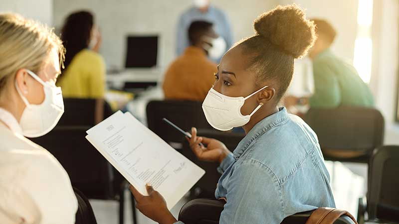 Black, female student in COVID mask talking with a fellow student, and holding a notepad.