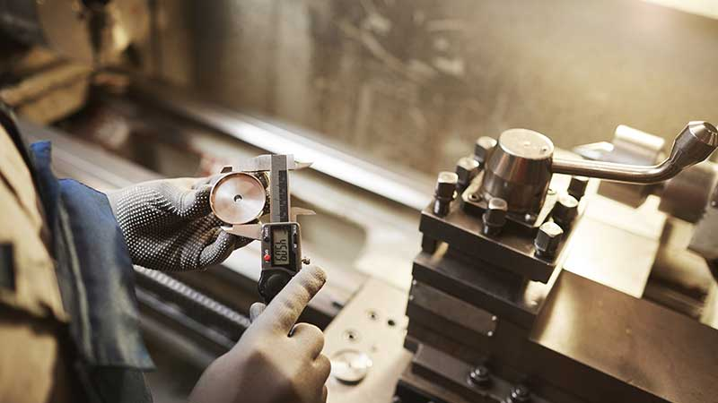 A technician measures a machined piece of round brass with calipers.