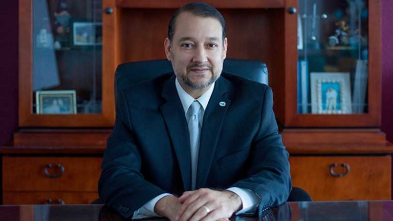 William Serrata sitting at a desk in a suit and tie.