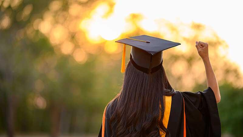 Woman in graduation mortar board raises her fist triumphantly toward the sunset.