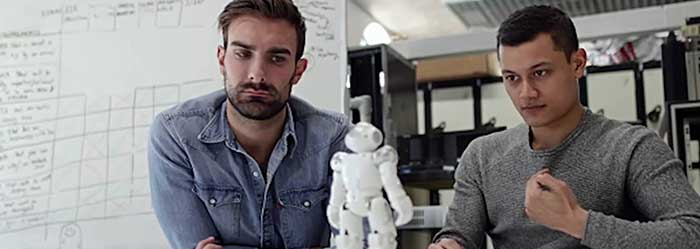 Two men work with a small tabletop robot unit.