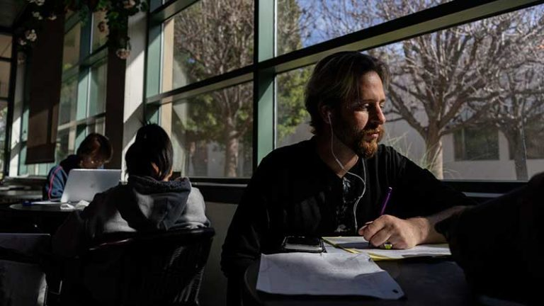 Student Zaq Woodward studies in a common area at a table in front of a window.