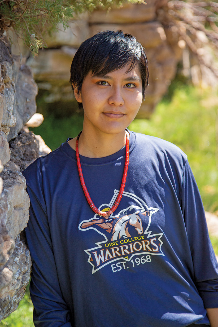 Female Navajo student in Diné College Warriors sweatshirt leans agains the rocks.