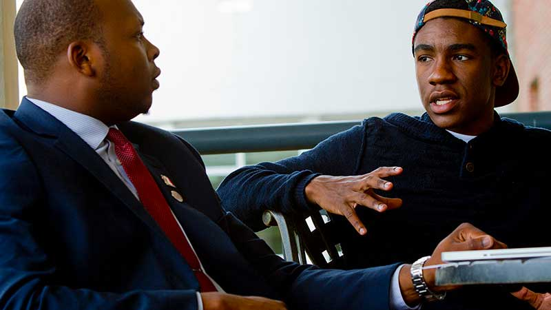 Two Black, male students confer.