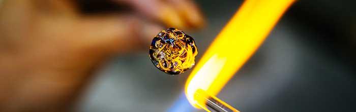 Glass artist melts a glass rod with a torch.