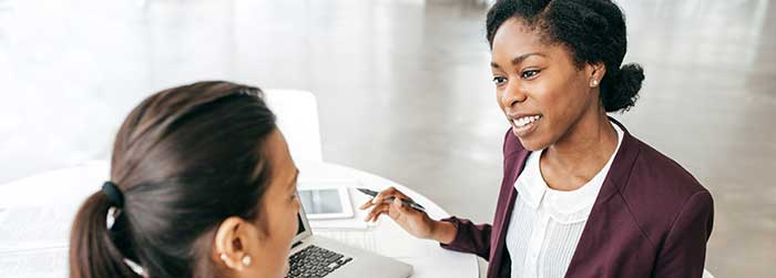 Two women work together in an office environment.