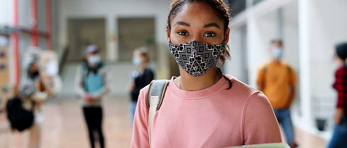 Black, female student in a pink sweater and covid mask, holding a pastel green binder. Other students can be seen chatting in the background.