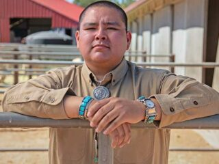 Navajo student Triston Black stands behind a livestock fence facing the camera.