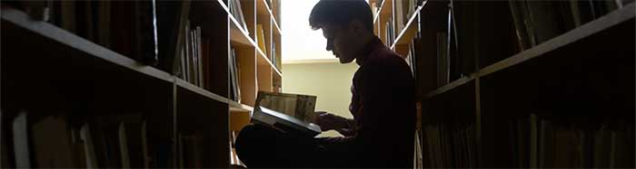 Man in library stacks in profile, sits reading.