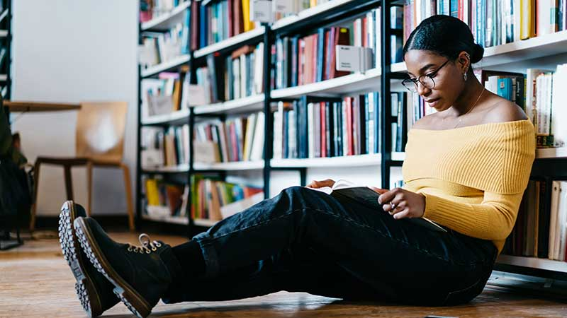 Black female student studies in a library.