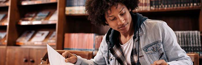 Black student studies in a library environment.